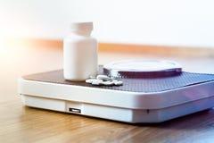 Dieetpillen op een schaal De geneeskunde van het gewichtsverlies stock afbeelding