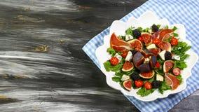 Dieetsalade met fig., arugulablad, schimmelkaas Dorblu, prosciutto en kersentomaten op de oude keukenlijst Vlak leg bovenkant vi royalty-vrije stock foto's