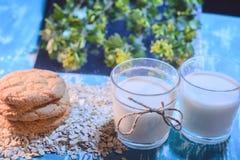 Dieetveganistvoedsel: havermeelmelk met koekjes in rustieke stijl op een bloemenachtergrond van een oude houten lijst stock afbeeldingen