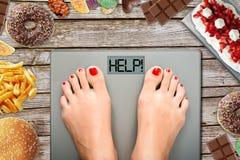 Dieetverleiding of moeilijk om gewichtsconcept te verliezen met vrouw het wegen op badkamersschaal met veel rond snoepjes en snel royalty-vrije stock afbeelding