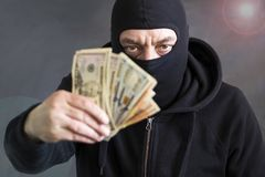 Dief in balaclava met in hand dollars corruptie steekpenning fraude stock afbeelding