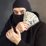 Dief in balaclava met in hand dollars corruptie steekpenning fraude stock fotografie