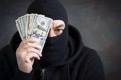 Dief in balaclava met in hand dollars corruptie steekpenning fraude stock foto