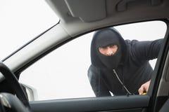 Dief die in auto met schroevedraaier breken stock foto's