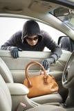 Dief stealing portefeuille van auto Stock Foto's