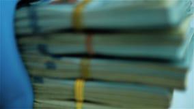 Dien blauwe handschoen in zet pakken Amerikaanse dollarbundels op witte oppervlakte Close-up stock footage