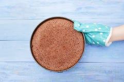 Dien de keukenvuisthandschoen in houdt een vorm met een gebakken chocoladekoekje op blauwe houten achtergrond stock afbeelding