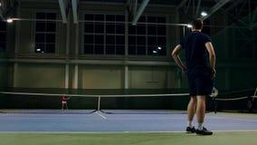 Dien door professionele tennisspeler Het tennis dient binnen van teniszaal De mens dient met tenisracket en binnen gekleed stock footage