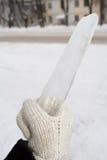 Dien gebreide vuisthandschoenen in houdt een grote ijskegel Stock Fotografie