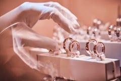 Dien handschoenen in neemt aan exclusieve ringen op de showcase van een juwelenopslag stock afbeelding