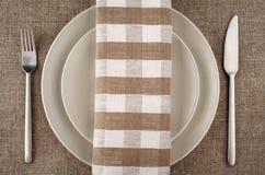 Dien het plaatsen in Beige plaat, vork, mes en beige linnenservet en tafelkleed Stock Foto