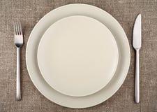Dien het plaatsen in Beige plaat, vork, mes en beige linnentafelkleed Stock Foto's