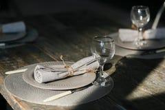 Dien het plaatsen in Paar lege grijze platen Mes en Vork Ouderwetse wijnglazen Rustiek servet Houten lijst Royalty-vrije Stock Fotografie
