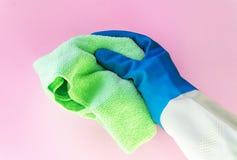 Dien kleur in de rubber beschermende handschoen een helder die microfiberstofdoek op de roze achtergrond wordt geïsoleerd houdt a stock foto