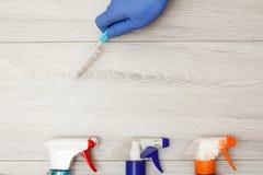 Dien rubber het stofborstel van de handschoenholding met flessen detergens in stock afbeeldingen