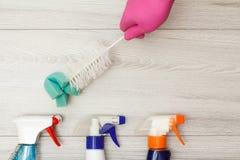 Dien rubber het stofborstel van de handschoenholding met flessen detergens in stock afbeelding
