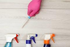 Dien rubber het stofborstel van de handschoenholding met flessen detergens in royalty-vrije stock foto