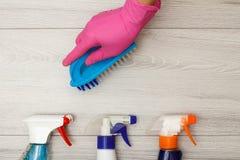 Dien rubber het stofborstel van de handschoenholding met flessen detergens in stock foto