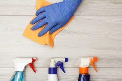 Dien rubber het stofservet van de handschoenholding met flessen detergens in stock afbeeldingen