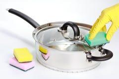 Dien rubberhandschoen schoonmakende het stoven pan in Stock Foto's
