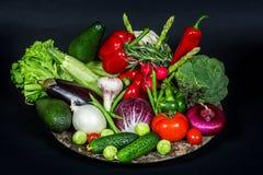 Dienblad met hoop van verse groenten op de zwarte achtergrond Royalty-vrije Stock Foto