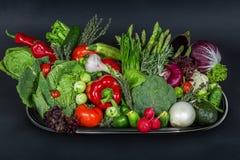 Dienblad met hoop van verse groenten op de zwarte achtergrond Stock Afbeeldingen