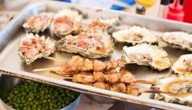 Dienblad met kebab van kammosselen en gebakken oesters stock foto's