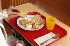 Dienblad met lunch en oude persoonshanden Royalty-vrije Stock Foto