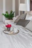Dienblad van bloem, theekoppen en boek op bed in slaapkamer Stock Afbeelding