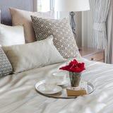 Dienblad van bloem, theekoppen en boek op bed in slaapkamer thuis Stock Afbeelding