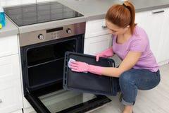Dienblad van de vrouwen het schoonmakende oven met vod royalty-vrije stock foto
