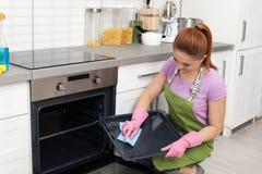 Dienblad van de vrouwen het schoonmakende oven met vod royalty-vrije stock afbeelding
