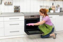 Dienblad van de vrouwen het schoonmakende oven met vod royalty-vrije stock foto's