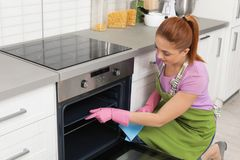 Dienblad van de vrouwen het schoonmakende oven met vod royalty-vrije stock fotografie