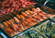 Dienblad van langoustines bij een zeevruchtenteller in een supermarkt stock fotografie