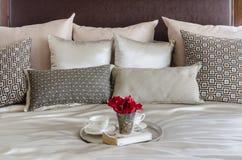 Dienblad van rode bloem, theekoppen en boek op bed Royalty-vrije Stock Foto