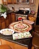 Dienbladen van voedsel in keuken stock afbeelding