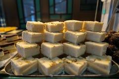 Dienbladhoogtepunt van cake van het stapel de heerlijke witte Indische zoete dessert met pistache in bakkerijshowcase Stock Foto