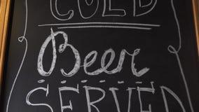 Diende het ambacht koude bier hier insctiption door wit krijt op zwarte raad Uitnodiging voor de bar van de brouwerijbar voor het stock footage