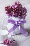 Dienend ontbijt: een kop en een kruik met lilac bloemen wordt verfraaid die Stock Foto's