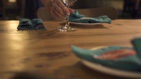 Dienende lijst in elegant restaurant Serveerster die wijnglas op lijst voor romantisch diner in luxerestaurant zetten stock footage