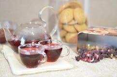 Dienende lijst voor ontbijt, rode thee in theepot theebladen, hibiscus en twee glaskoppen met rode thee royalty-vrije stock fotografie