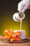 Dienende melk met wit aardewerk Royalty-vrije Stock Foto