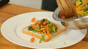 Dienende Mischung des gebratenen Gemüses auf einem Toast stock video