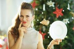 Dienender weißer großer Teller der nachdenklichen jungen Hausfrauholding stockfoto