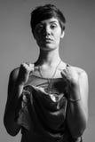 Dient de kort-haar donkerbruine vrouw die een mouwloos onderhemd met haar houden B in Stock Fotografie
