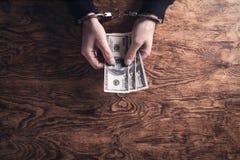 Dient handcuffs in houdend dollarbankbiljetten corruptie royalty-vrije stock fotografie