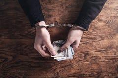 Dient handcuffs in houdend dollarbankbiljetten corruptie stock foto