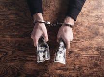 Dient handcuffs in houdend dollarbankbiljetten corruptie royalty-vrije stock foto