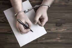 Dient handcuffs in schrijven een opkomst op de achtergrond van een houten lijst royalty-vrije stock afbeeldingen